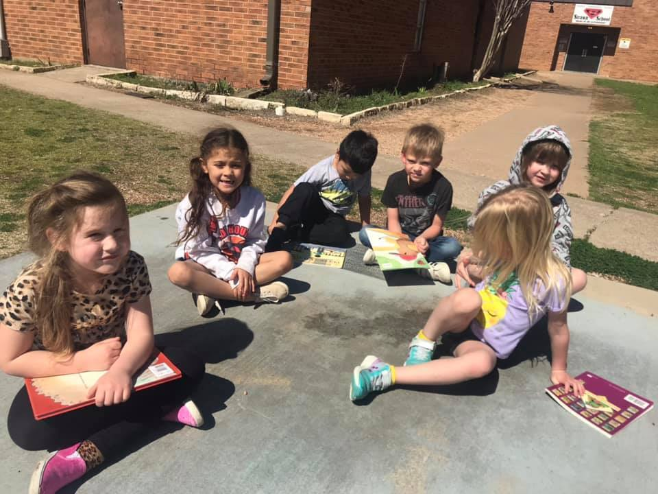 PreK soaks up the sun by reading outside!