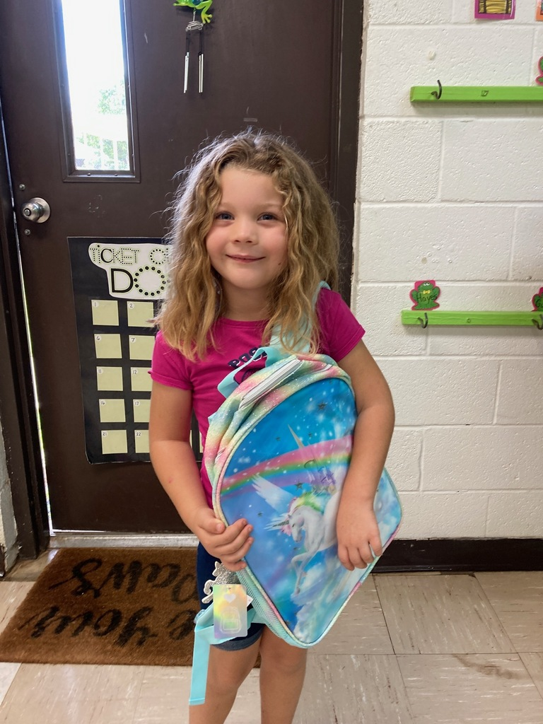 Lily receives her backpack for completing Summer School!
